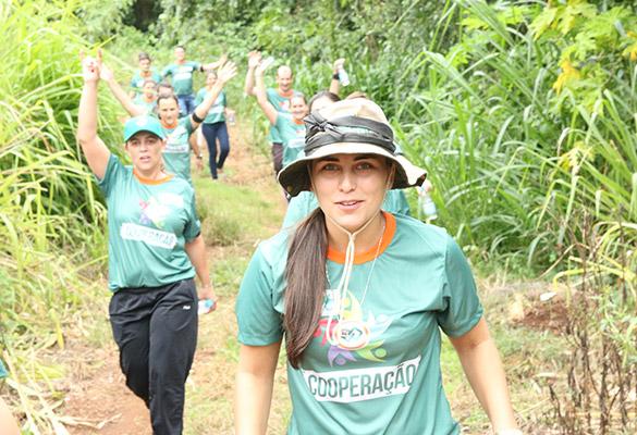 Mulher com olhar de determinação tomando a frente de uma equipe durante uma trilha em meio à vegetação.